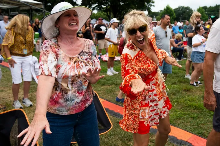 Cindy Dahl, left, and Carol Kaminski dance to the musical comedy of Craig Robinson and the Nasty Delicious at the Hoagie Nation festival, starring Hall & Oates, Squeeze, and Kool & the Gang on Saturday.