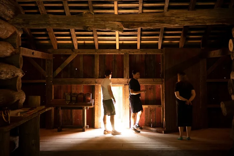 The original Jones Log Barn was two stories and built into an embankment. In the top level of the restored version, Steve Miller (center), who designed the exhibits, speaks with Pattye Benson (right), president of the Tredyffrin Historic Preservation Trust.