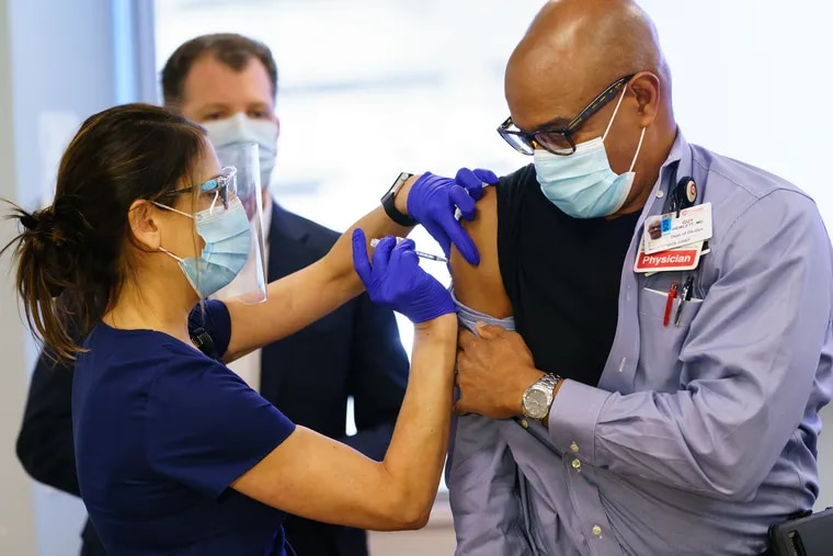 LPN Kimberly Peacock, left, administers the Covid-19 Vaccine shot to Dr. Guy Hewlett, M.D., right, at Cooper University Health Care,Tuesday, December 15, 2020. Cooper University Health Care is among the first group of hospitals in New Jersey to receive the new COVID-19 vaccine