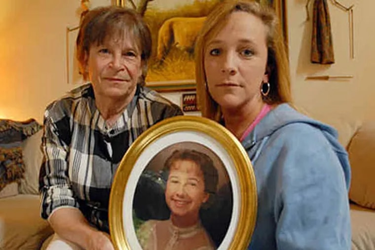 For Diane Mozino to move forward, she says, she needs to find her daughter Dawn and to give her a proper burial. She and daughter Cathy Mozino-Miesen hold a portrait of Dawn Mozino.