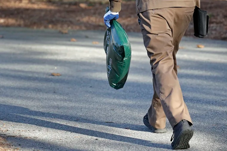 In this Nov. 26, 2019, photo a UPS man delivers a package to a residence in North Andover, Mass. Here are tips on how to order online and save money.