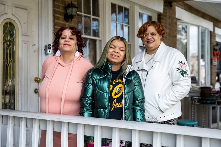 Angelique Howard, 44, of North Philadelphia, (left) poses for a portrait with her daughter, Angelique Howard-Johnson, 16, (center), and sister Gabrielle Howard, 55, at her home. The Howard family was able to straighten out the home's tangled title thanks to a city program that provides free legal help and waives and defers fees. The Howards want to fix the home and renovate the space, but they couldn't get financial help to do so previously because the title was under their mother's name.