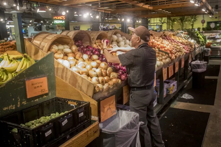 A customer looks through the onion selections at Iovine Brothers Produce at the Reading Terminal Market in Philadelphia. The market sees more food-stamp purchases than almost any other single location in Pennsylvania.