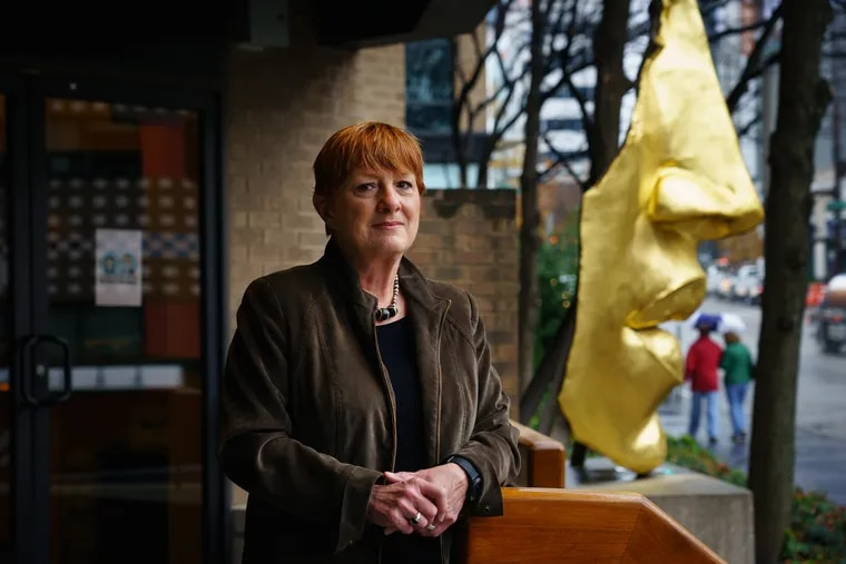 """Pam Dalton, a scientist who studies the nose, including mucus, stands outside the Monell Chemical Senses Center, in front of the sculpture """"Face Fragment,"""" by Philadelphia sculptor Arlene Love."""