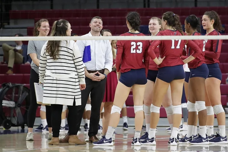 Penn volleyball head coach Iain Braddak (center) with his assistant coaches and some of his players during a match at the Palestra this season.