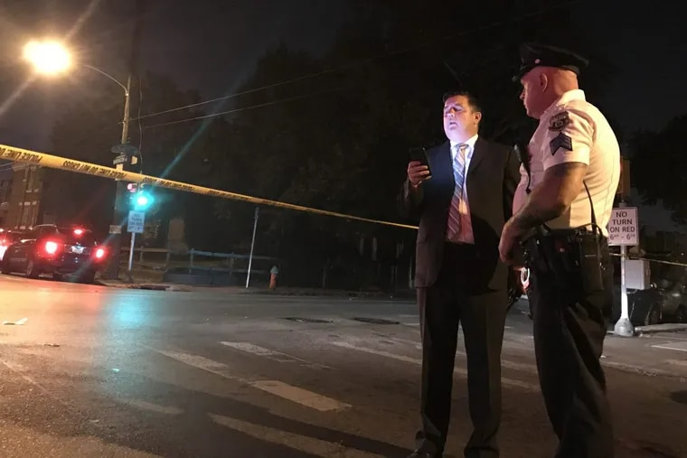 Lt. John Walker, left, checks his phone at the scene of a shooting on 54th Street and Warrington Avenue on Sept. 28, 2017.