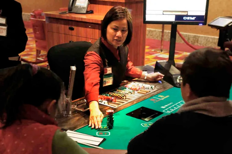 Aileen Chiu deals baccarat in the Parx East Casino. New games include pai gow, pai gow tiles, Sic Bo, and mini- and midi-baccarat, all popular among Asian gamblers.