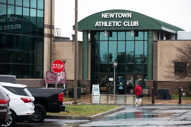 People walk into the Newtown Athletic Club in Newtown, Pa., on Monday. The Newtown Athletic Club remains open despite Gov. Tom Wolf's most recent mitigation order that requires gyms to halt indoor operations.