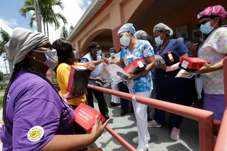Union members hand out masks to prevent the spread of the new coronavirus and lunches to workers at the Franco Nursing & Rehabilitation Center, Monday, July 20, 2020, in Miami. Workers need a voice in their workplaces now more than ever, writes Jennifer Dorning, President of the Department for Professional Employees, AFL-CIO.