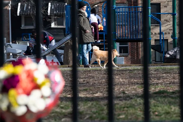 """Metra LeBlanc walks her dog """"Lea"""" pass a bouquet of flowers on a fence at the Gold Star Park in South Philadelphia. A South Philadelphia dog walker was killed in front of his fiancee in January 2019 after a dispute with another dog walker at Gold Star Park."""