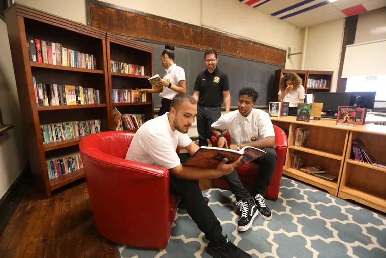 Teacher Eric Cruz (center) with (clockwise from left) seniors Michael Lugo,  Brietney Vega, Britney Rivera and Manny Rivera in the library that engineering students are creating at Kensington High School.