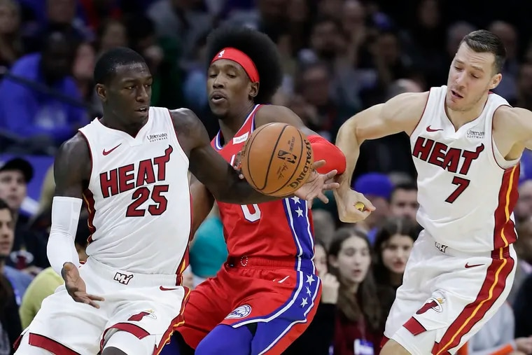 Sixers guard Josh Richardson attempts the steal the basketball against Miami Heat guard Kendrick Nunn and past Miami Heat guard Goran Dragic (right) during the first-quarter on Saturday, November 23, 2019 in Philadelphia.  Richardson fouled Nunn on the play.