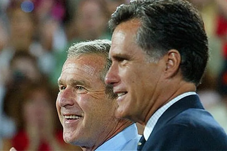 In this Aug. 30, 2004 file photo, President George W. Bush is introduced by Massachusetts Gov. Mitt Romney at a campaign rally in Nashua, N.H. Expect Bush to stay far away from this year's presidential election. (AP Photo / Pablo Martinez Monsivais, File)