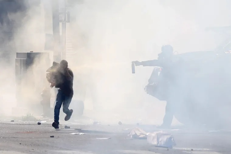 A person runs through a cloud of tear gas while being sprayed with a chemical after police dispersed a large crowd near the Foot Locker at 52nd and Chestnut streets in Philadelphia on Sunday, May 31, 2020.
