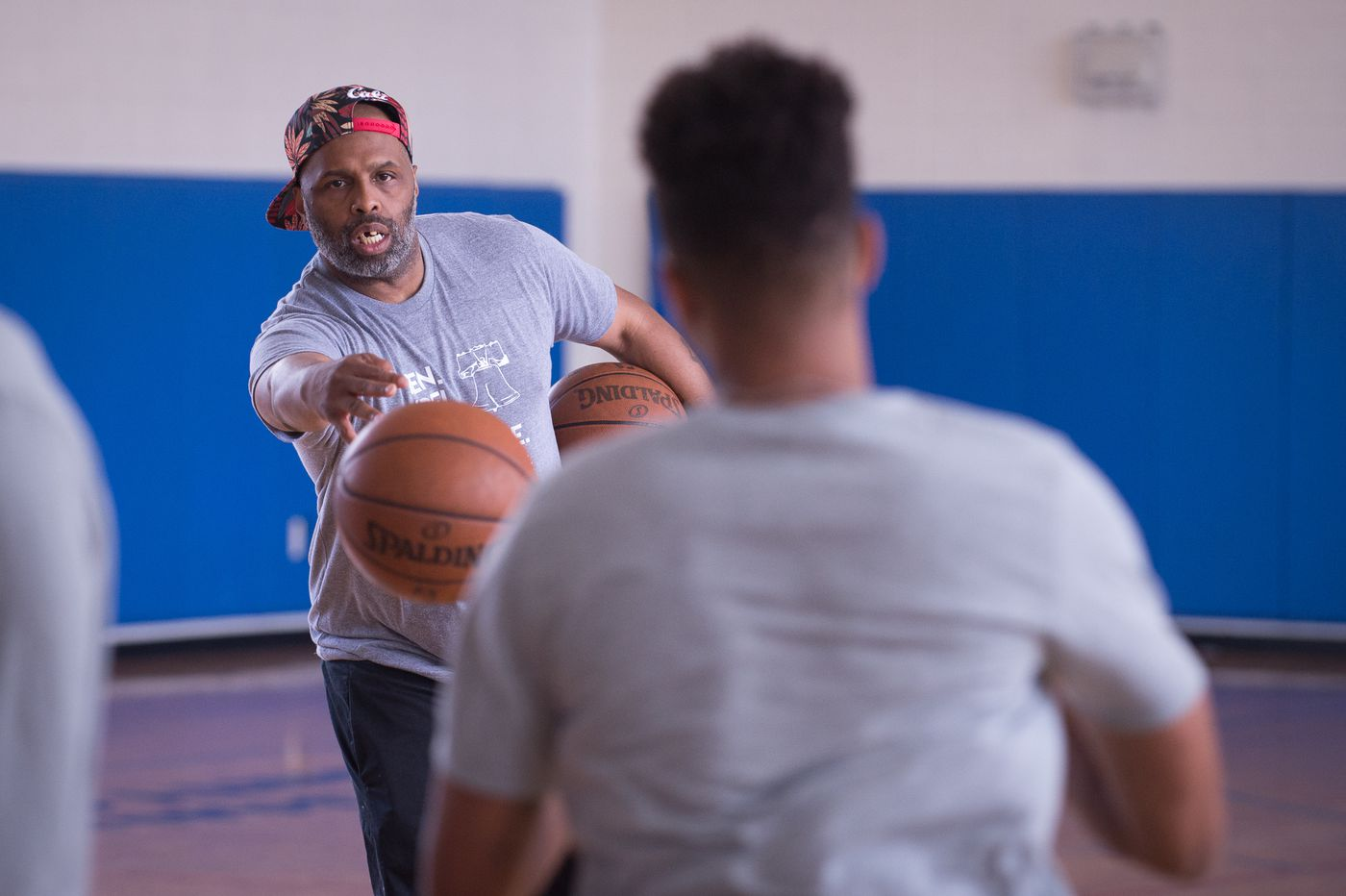 Keith Williams, longtime trainer of Markelle Fultz (front), throws Fultz a ball during drills at the Riggs LaSalle Recreation Center in Washington, DC, June 27th, 2017. CAMERON B. POLLACK / Staff Photographer