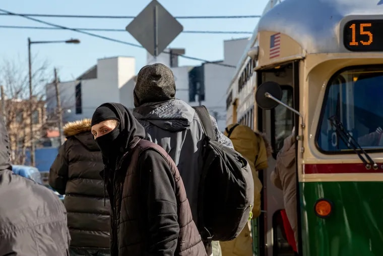 A transit customer wearing a mask to stay warm waits to board the trolley at the intersection of Girard Avenue and Front Street in Fishtown.