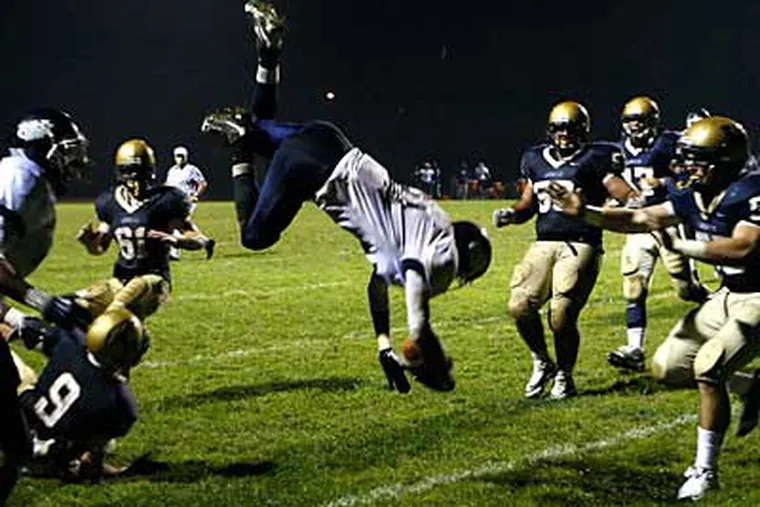 W. Catholic's Brandon Hollomon flies over a host of would be LaSalle's tacklers. (Ron Cortes / Staff Photographer)