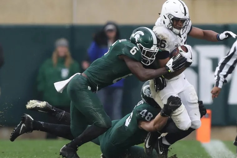 Michigan State's Davis Dowell and Kenny Willekes tackle Penn State's Saquon Barkley in the third quarter