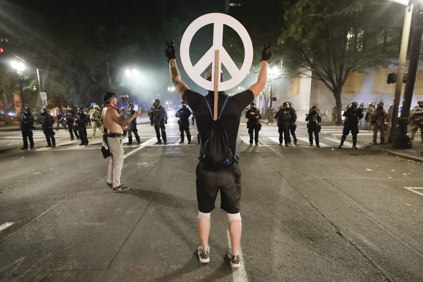 A demonstrator flashes a peace sign at federal officers during a Black Lives Matter protest at the Mark O. Hatfield United States Courthouse Wednesday, July 29, 2020, in Portland, Ore. (AP Photo/Marcio Jose Sanchez)