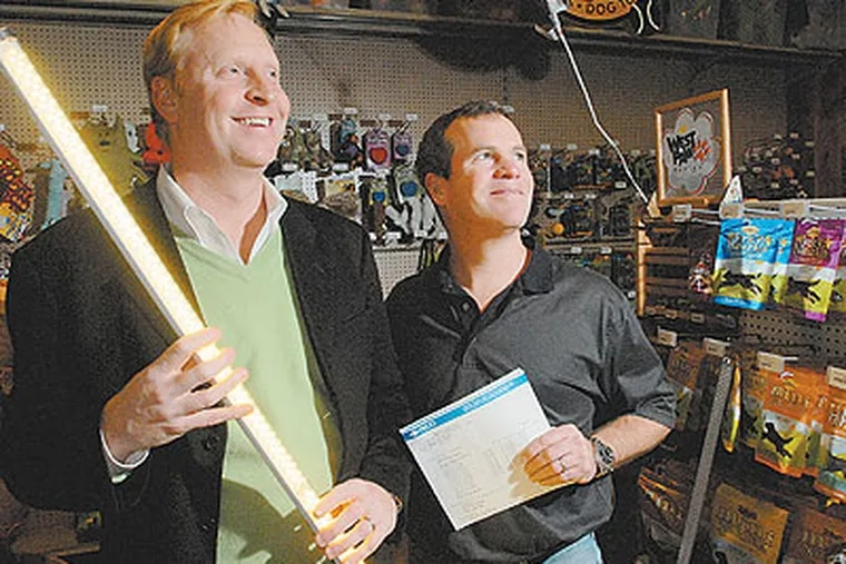 Charles Szoradi, holding a LED replacement light for flourecent tube fixtures, stands with client David Braxton, of Braxton's Animal Works. (Bob Williams / For The Inquirer)