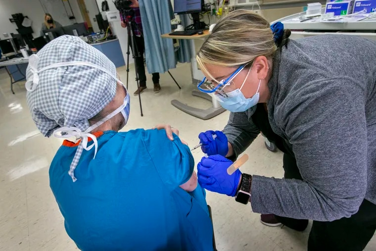 Registered Nurse Erin Gallagher administers the COVID-19 vaccine to Bonnie Karpo, operating room nursing educator, at St. Christopher's Hospital for Children last month.