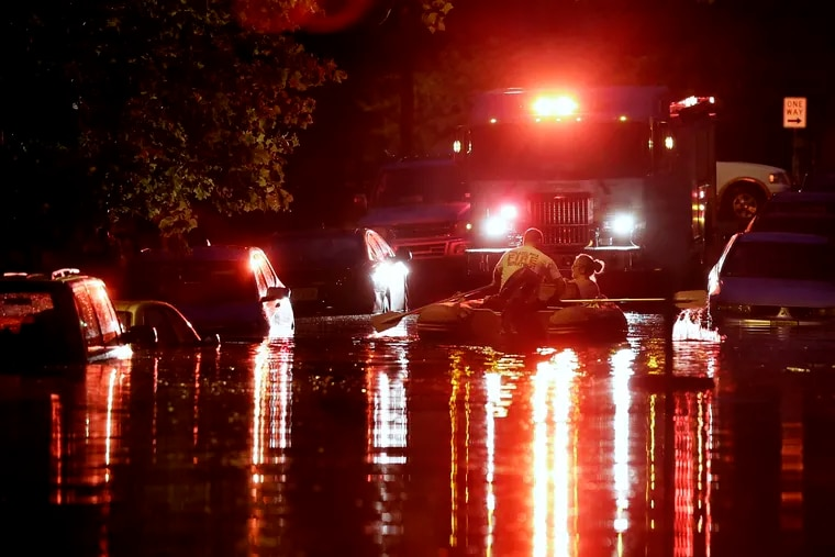 A woman is evacuated from the rising flood water on High St. after overnight thunderstorms flooded much of Westville on Thursday.