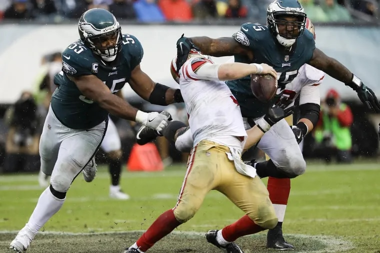 Eagles defensive ends Brandon Graham and Vinny Curry converge on San Francisco quarterback C.J. Beathard earlier this season. They'll be looking for Dak Prescott of Dallas this Sunday. YONG KIM / Staff Photographer