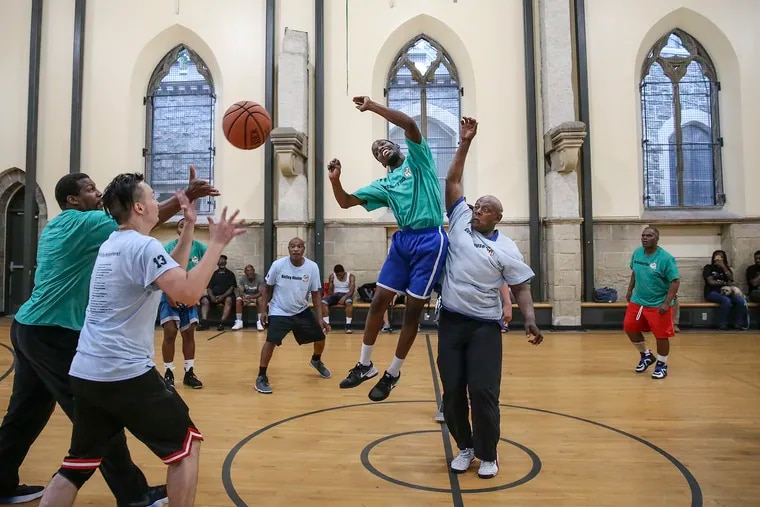 Players from the Outley House go up against Our Brothers' Place during a game at the Church of the Advocate in North Philly on Wednesday. Men from both shelters participate in a basketball league run by Hoops for Hope.