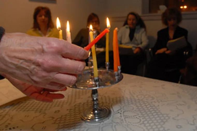 """""""People are really fragile around this time,"""" says Rabbi Tsurah August, lighting a candle for a """"Lightsin the Darkness"""" program at the Joan Grossman Center for Chaplaincy and Healing in Elkins Park."""