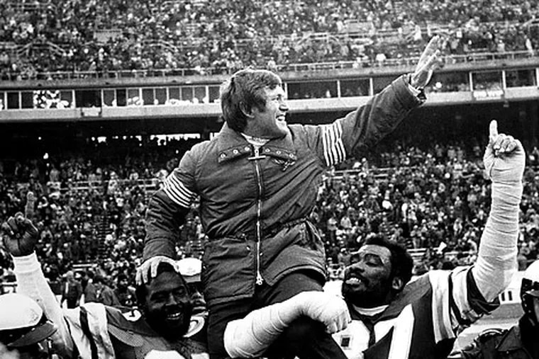 Dick Vermeil is carried off the field by his players after a win.