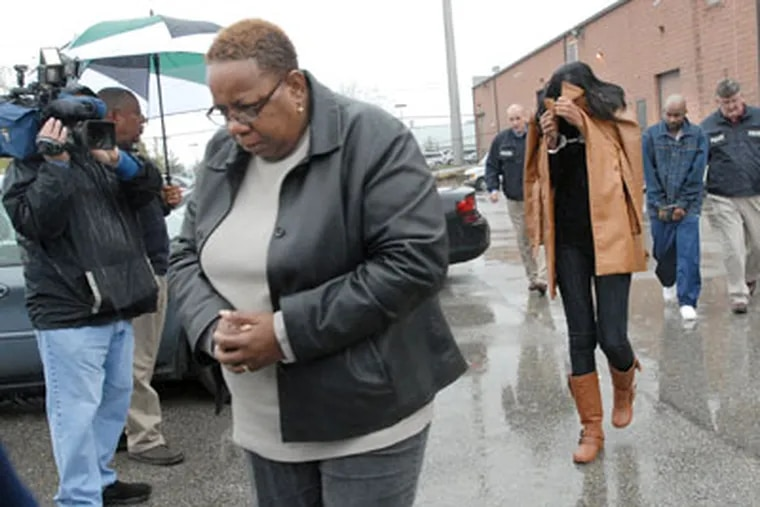 Among those arrested yesterday were Gail Polk (foregound), from whose work computer the counterfeit checks were determined to have been created, authorities allege. (April Saul / Staff photographer)