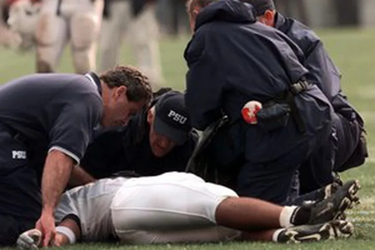 Trainers examined Penn State's Adam Taliaferro after he was left paralyzed while making a tackle in 2000.