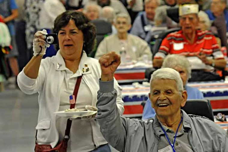 The Nj Veterans Memorial Home in Vineland, NJ was supposed to have a parade, but rain forced the festivities indoors on 5/11/13.  Here, C. Anthony Confalone of Vineland raises his arm in a celebratory manner as the crowd sings happy birthday to Frank Cuccia, who turned 105 last month.  ( APRIL SAUL / Staff )