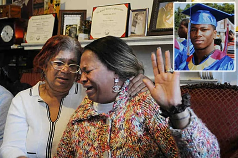 Javese Phelps-Washington (right) is comforted by her mother, Shirley Phelps-Pollard, while talking about her son, Christopher Spence (upper right). (Sarah J. Glover / Staff Photographer)