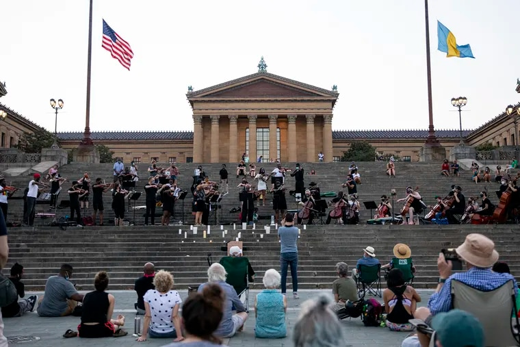 Musicians gather on the steps of the Philadelphia Art Museum for a musical candlelight vigil, with performances by a string ensemble, on July 19.