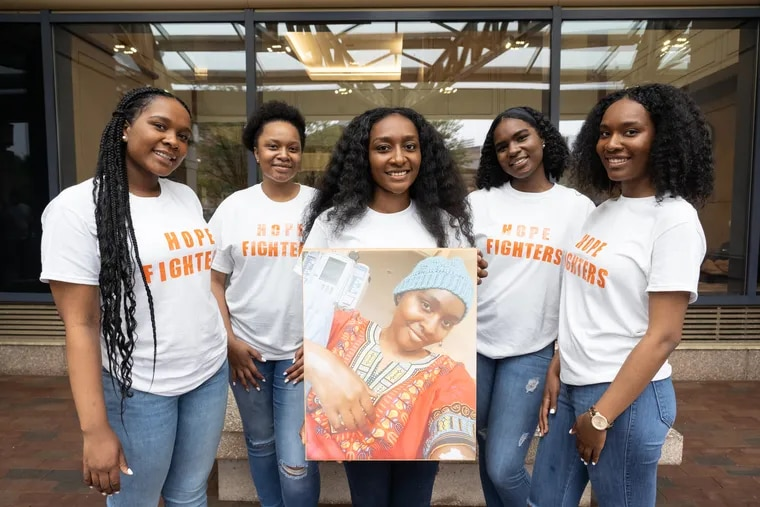 (from left) Sisters Joy Wells, Glory Wells, Charity Wells, Grace Wells, and Faith Wells shown here outside Hospital of the University of Pennsylvania holding a photo of their sister Hope Wells, who has been battling cancer for two years.