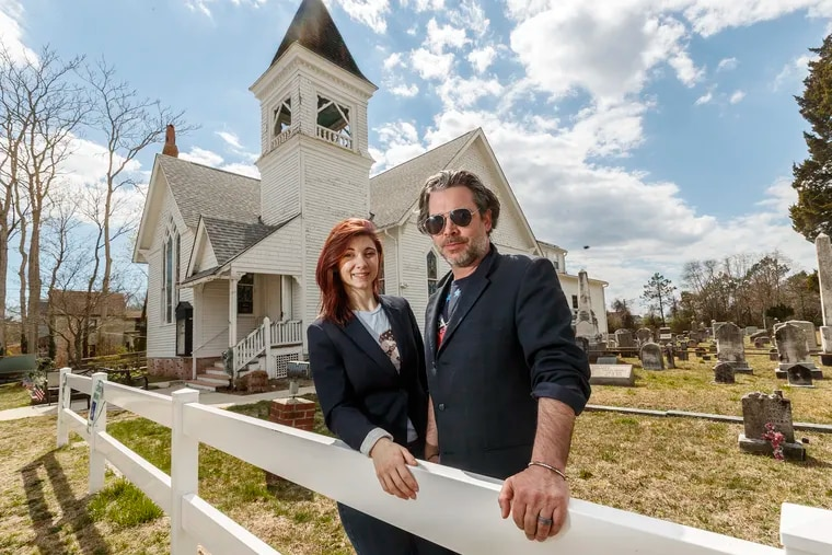 Will Keenan, right, the executive director and founder of St. Bab's, with Maura Allsman, left, the program director, in front of the cemetery and church that he bought two years ago and named after his late mother. The historic building has become a thriving spiritual, cultural, service, and advocacy center. Two Philadelphia organizations are partnering to help preserve the property on Delsea Drive in the hamlet of Goshen, Cape May County, NJ