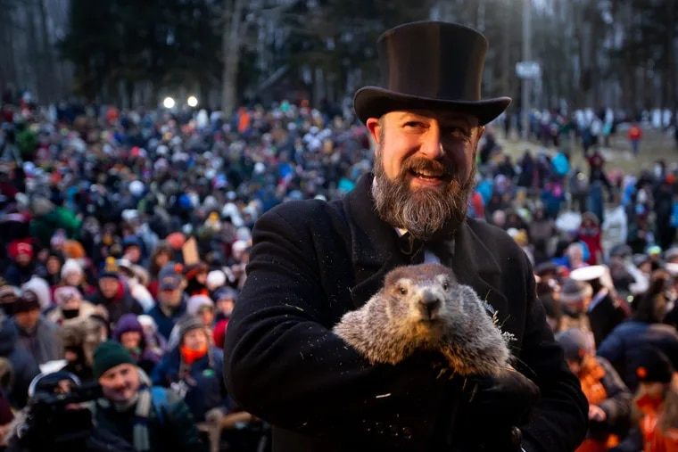 A member of the Punxsutawney Groundhog Club's inner circle holds Phil after he makes his weather prediction on Groundhog Day at Gobbler's Knob. With no shadow in sight, expect an early spring, unless you believe government experts, who say Phil's record is more wrong than right.