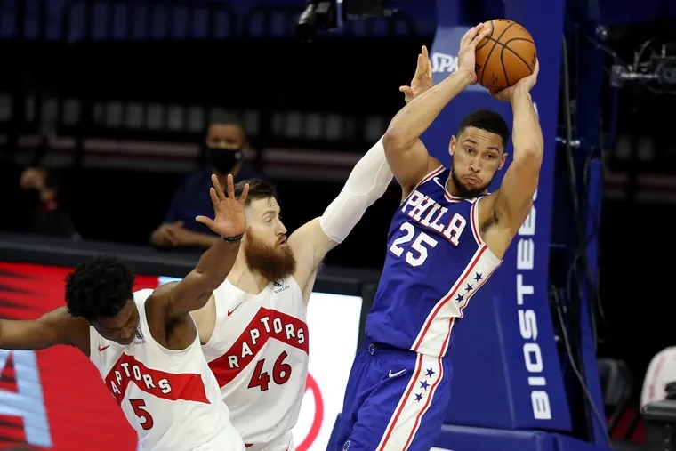 Ben Simmons, right, of the SIxers passes to a teammate after the Stanley Johnson, left, and Aron Baynes of the Raptors converge upon him during the 2nd half of a NBA game at the Wells Fargo Center on Dec. 29, 2020.