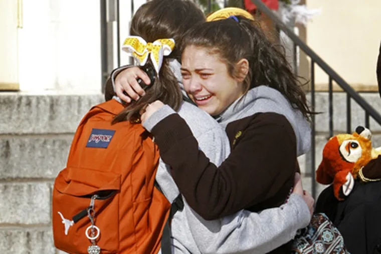 Students from St. Hubert High School console each other after leaving school Friday after learning that their school will close. (Alejandro A. Alvarez / Staff Photographer)
