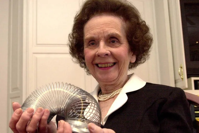 In this Jan. 18, 2001 file photo, Betty James, retired president of James Industries, plays with a toy Slinky that made the family company famous in Hollidaysburg, Pa. (AP Photo/The Altoona Mirror, J.D. Cavrich, File)