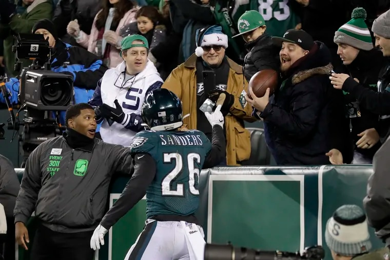 Eagles running back Miles Sanders tossed the ball to a fan in the front row at Lincoln Financial Field after his one-yard touchdown run in Sunday's win over the Dallas Cowboys.