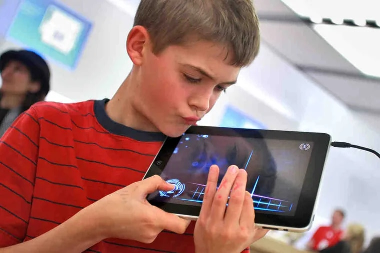 Using the Magic Fiddle app on an iPad, Ben Clark, 10, learns to play at an Apple Store workshop in Palo Alto, Calif. Touchscreen technology and child-friendly downloads are spurring a new era.