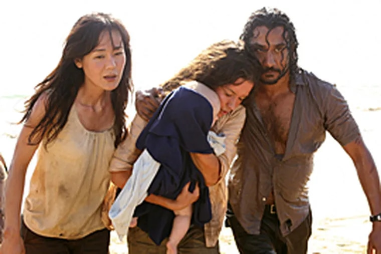 """Yunjin Kim, Evangeline Lilly, holding a baby, and Naveen Andrews are shown in a scene from the season finale of """"Lost."""" (AP/ABC)"""