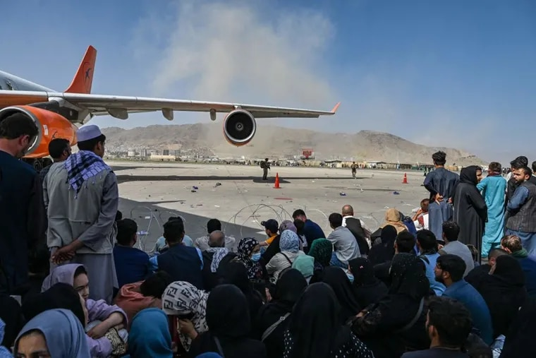 Afghan people sit as they wait to leave the Kabul airport on Aug. 16, 2021, after a swift end to Afghanistan's 20-year war, as thousands of people mobbed the city's airport trying to flee the Taliban's feared hardline brand of Islamist rule.