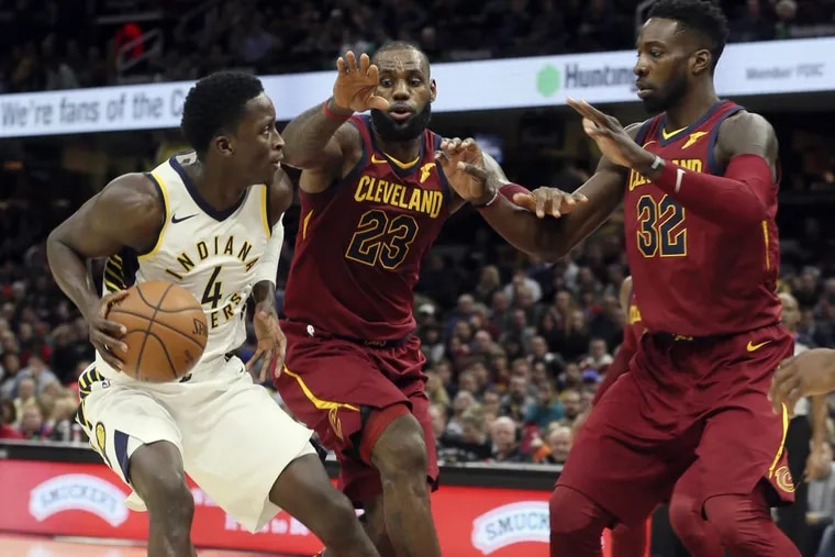 The Indiana Pacers' Victor Oladipo (4) is defended by Cleveland Cavaliers LeBron James (23) and Jeff Green (32) on Wednesday.