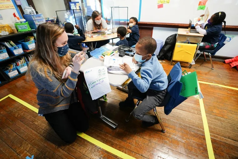 Student teacher Sophia Bonavolonta, left, works with student Aiden Moore at Belmont Charter School in February. Teachers are in Pennsylvania are now being vaccinated.