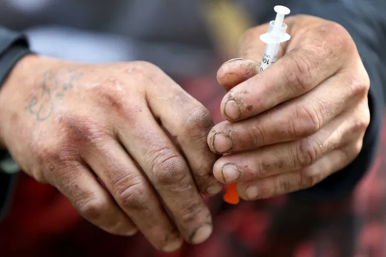Robert Hilton holds on to a needle after using heroin along the railroad track in Kensington in 2017.