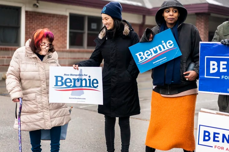 A New Hampshire voter is offered a Bernie Sanders campaign sign after casting her vote at a polling location in Nashua, N.H., on Tuesday.