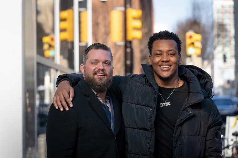 Foster father Jackson Duncan, left, founder of Focused Athletics, a non-profit that helps Philadelphia inner-city high school athletes, and College freshman Zymir Cobbs shown here outside family court, after Cobbs is officially adopted by Duncan, in Philadelphia, January 15, 2020.
